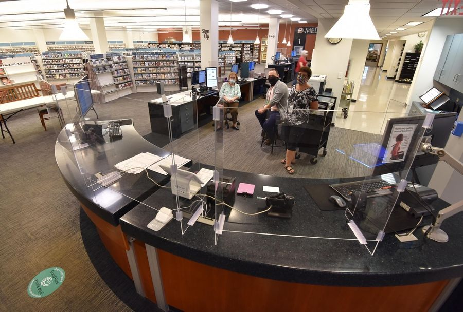The checkout counter has plexiglass partitions at the Gail Borden Public Library in Elgin.