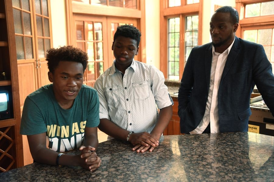 Standing in the kitchen of the Inverness mansion he had been living in for about a year, Allen Smith talked about what life was like since leaving Chicago's South Side. With him were K.J. Collins, middle, and Terrence Wallace, founder of the InZone Project. Now, Wallace wants to move 25 children of color into a Barrington Hills mansion.
