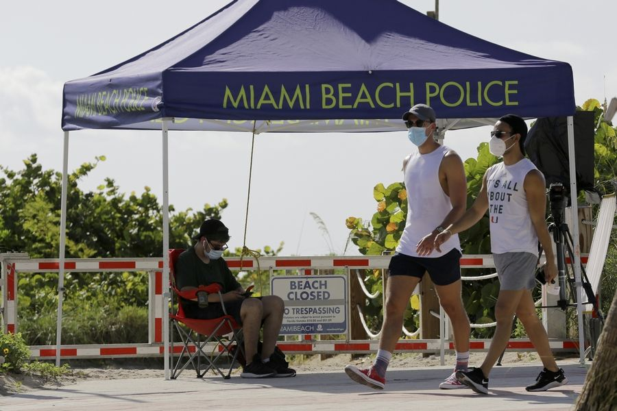 People wearing protective face masks walk past a closed entrance to the beach Friday in the South Beach neighborhood of Miami Beach, Floria. Beaches throughout South Florida are closed for the busy Fourth of July weekend to avoid further spread of the new coronavirus.