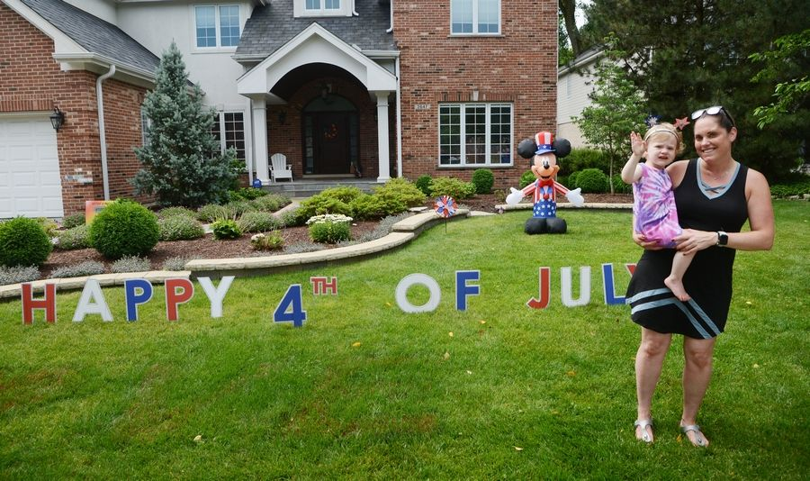 Jacki Ruh, with her daughter, Eleanor, 2, and her family have decorated the exterior of their home for Northbrook's 4th of July Porch Parade.
