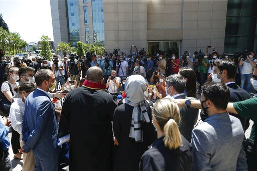 Hatice Cengiz, centre back to camera, the fiancee of slain Saudi journalist Jamal Kashoggi, talks to members of the media outside a court in Istanbul, Friday, July 3, 2020, where the trial in absentia of two former aides of Saudi Crown Prince Mohammed bin Salman and 18 other Saudi nationals over the 2018 killing of the Washington Post columnist had began. Turkish prosecutors have indicted the 20 Saudi nationals over Khashoggi's grisly killing at the Saudi Consulate in Istanbul that cast a cloud of suspicion over Prince Mohammed and are seeking life prison terms for defendants who have all left Turkey. Saudi Arabia rejected Turkish demands for the suspects' extradition and put them on trial in Riyadh.