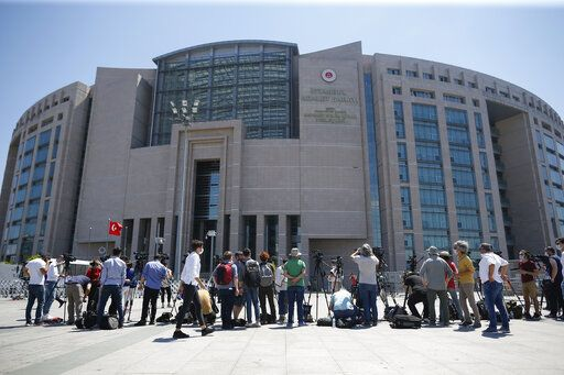 Members of the media, work outside a court in Istanbul, Friday, July 3, 2020, where the trial in absentia of two former aides of Saudi Crown Prince Mohammed bin Salman and 18 other Saudi nationals over the 2018 killing of Saudi journalist Jamal Kashoggi had began. Turkish prosecutors have indicted the 20 Saudi nationals over Khashoggi's grisly killing at the Saudi Consulate in Istanbul that cast a cloud of suspicion over Prince Mohammed and are seeking life prison terms for defendants who have all left Turkey. Saudi Arabia rejected Turkish demands for the suspects' extradition and put them on trial in Riyadh.