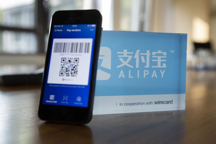 An Alipay digital payment app logo and smartphone sit on a desktop in Munich, Germany, on Sept. 5, 2018.