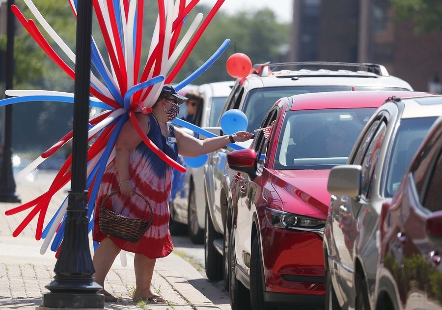 Karen Pawlak of Baird and Warner hands out mini flags Saturday before a Fourth of July Parade in the Baird & Warner parking lot in Arlington Heights. Participants were stationed in the parking lot at 210 W. Northwest Highway, and visiting cars drove by to wave to veterans and the mayor, enjoy live music and more.