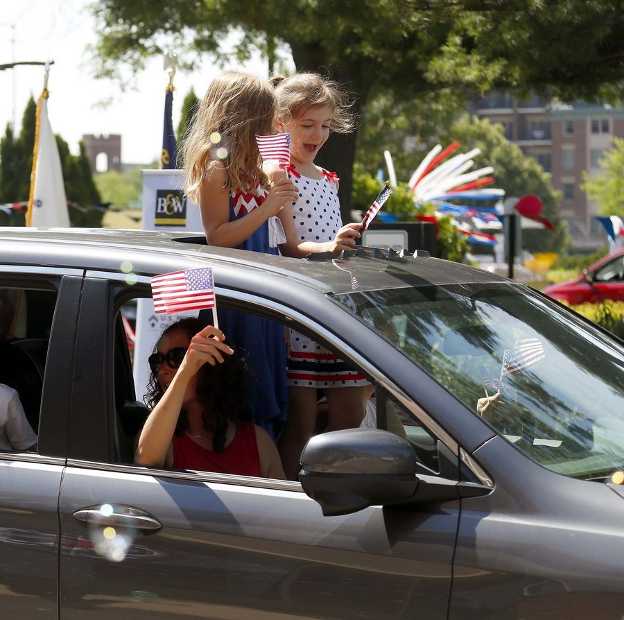 Gracie Vercimak, 5, left in blue, and her cousin Leah Parks, 7, stand in the opening of a sun roof as Allison Vercimak of Arlington Heights waves a flag from the passenger window Saturday during a Fourth of July Parade in the Baird & Warner parking lot in Arlington Heights.