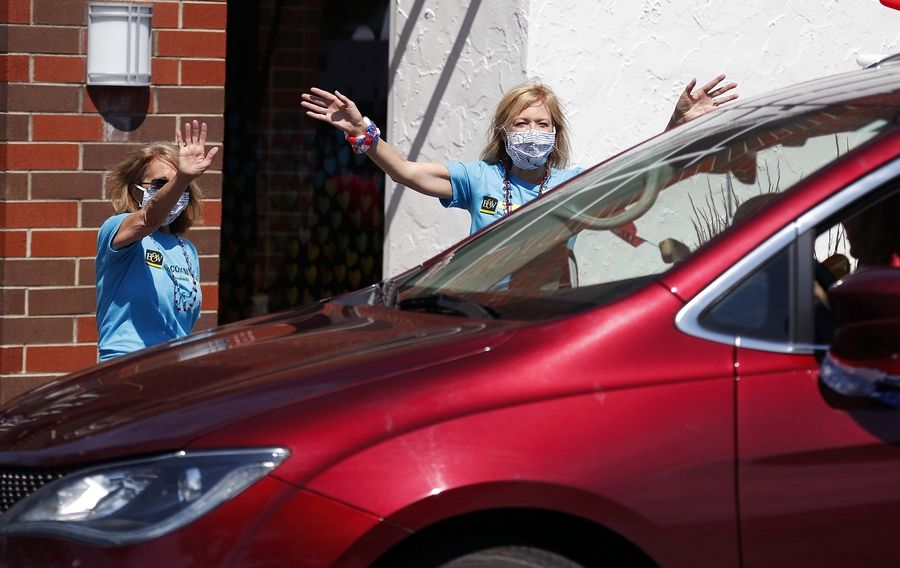 Diane Jamieson, left, and Shaunna Burhop, of Baird and Warner, wave to vehicles Saturday during a Fourth of July Parade in the Baird & Warner parking lot in Arlington Heights.