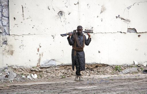 A Somali soldier stands at the scene of a suicide car bomb near the port in Mogadishu, Somalia Saturday, July 4, 2020. Explosions rocked two of Somalia's largest cities on Saturday as officials said a suicide car bomber detonated near the port in Mogadishu and a land mine was detonated by remote control as people were dining in a restaurant on the outskirts of Baidoa.