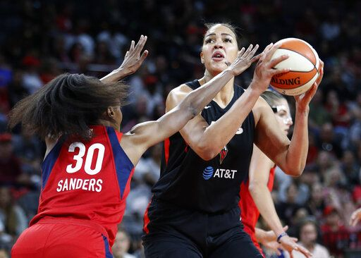 FILE - In this Tuesday, Sept. 24, 2019, file photo, Las Vegas Aces' Liz Cambage shoots against Washington Mystics' LaToya Sanders during the first half of Game 4 of a WNBA playoff basketball series in Las Vegas. All-Star center Cambage is expected to miss the upcoming 2020 WNBA season for health reasons, according to her agent.