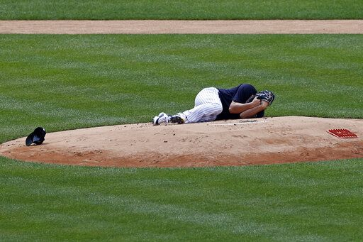 New York Yankees pitcher Masahiro Tanaka lies on the field after being hit by a ball off the bat of Yankees Giancarlo Stanton during a baseball a workout at Yankee Stadium in New York, Saturday, July 4, 2020.