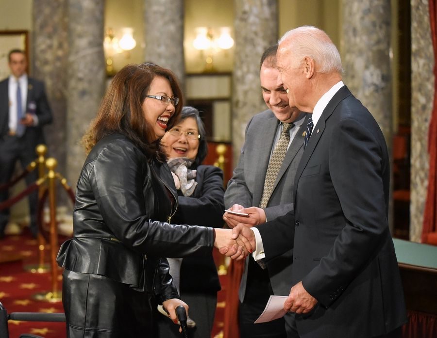 Then-Vice President Joe Biden shakes hands with Sen. Tammy Duckworth during a mock swearing in ceremony Jan. 3, 2017, in Washington. The presumptive Democratic presidential nominee is strongly considering Illinois' junior senator to be his running mate, sources close to the campaign say.