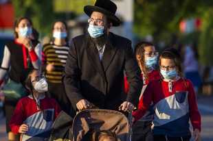 Ultra-Orthodox Jews wait to cross a closed road to go to their homes as they wear protective face masks to help curb the spread of the coronavirus in Ashdod, Israel, Thursday, July 2, 2020. Coronavirus restrictions have gone into effect in Israel after the number of new cases there hit a record high the previous day, while the West Bank prepares to go into lockdown. (AP Photo/Ariel Schalit)