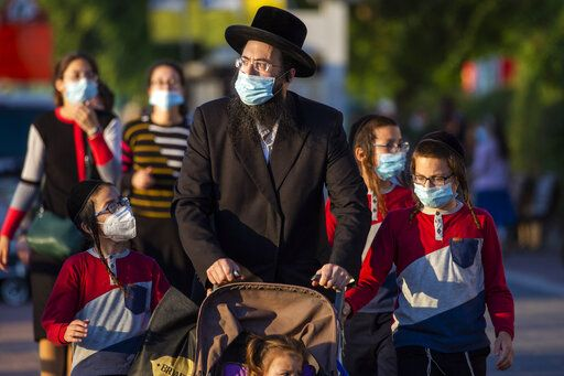 Ultra-Orthodox Jews wait to cross a closed road to go to their homes as they wear protective face masks to help curb the spread of the coronavirus in Ashdod, Israel, Thursday, July 2, 2020. Coronavirus restrictions have gone into effect in Israel after the number of new cases there hit a record high the previous day, while the West Bank prepares to go into lockdown.