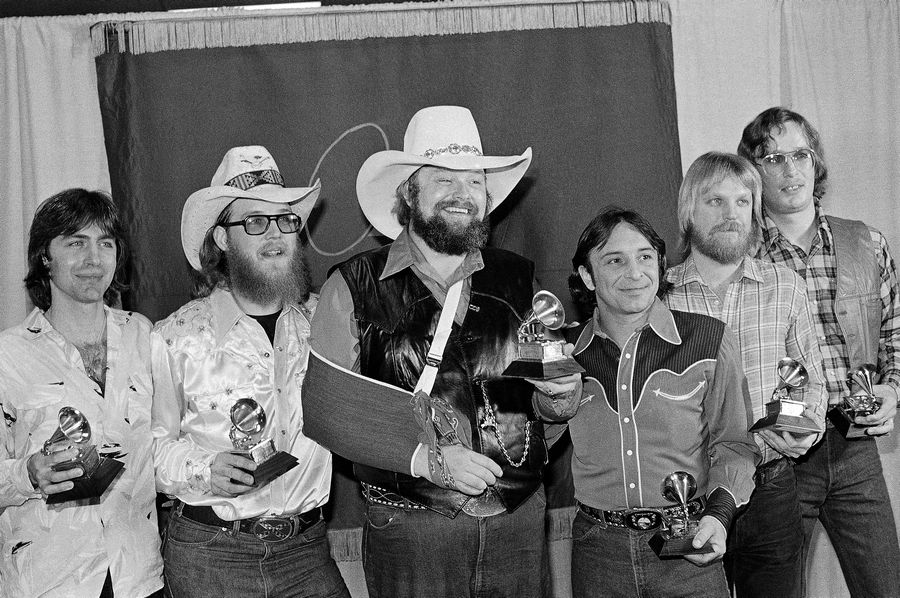 "Charlie Daniels, center, joins members of the Charlie Daniels Band with their Grammy Awards in Los Angeles on Feb. 27, 1980, as best country vocal performance by a group for their hit ""The Devil Went Down To Georgia."" Daniels has died at age 83. A statement from his publicist said the Country Music Hall of Famer died Monday, July 6, 2020, due to a hemorrhagic stroke."