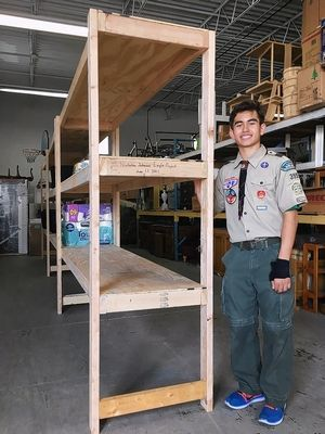 Nick Johnson of Hoffman Estates stands next to the shelving units he built at WINGS in Rolling Meadows as part of his Eagle Scout project.