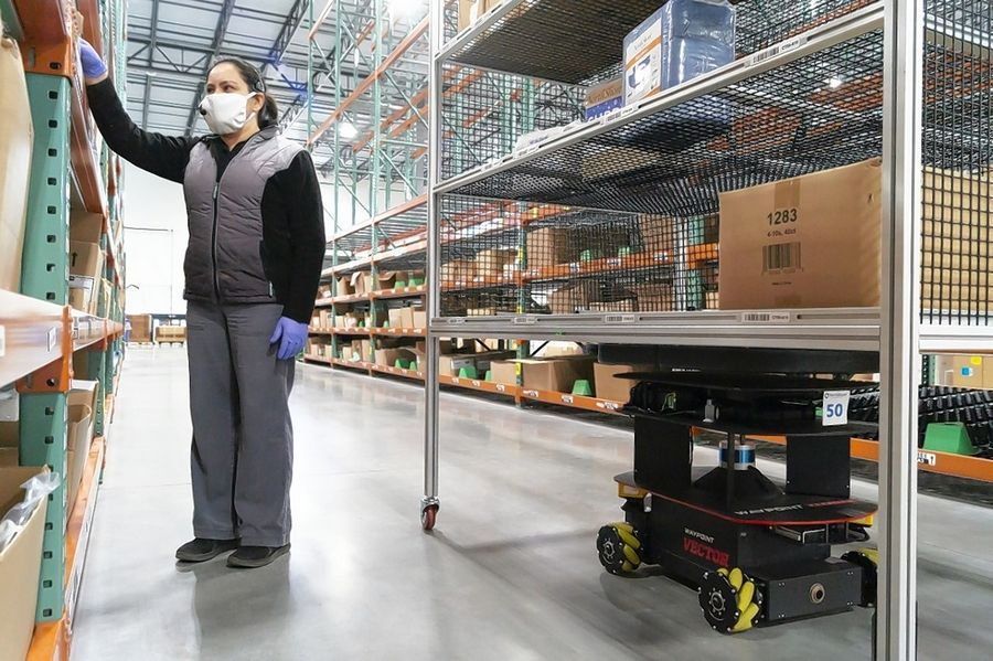 An autonomous mobile robot assists a warehouse worker with order filling at NorthShore Care Supply in Green Oaks.