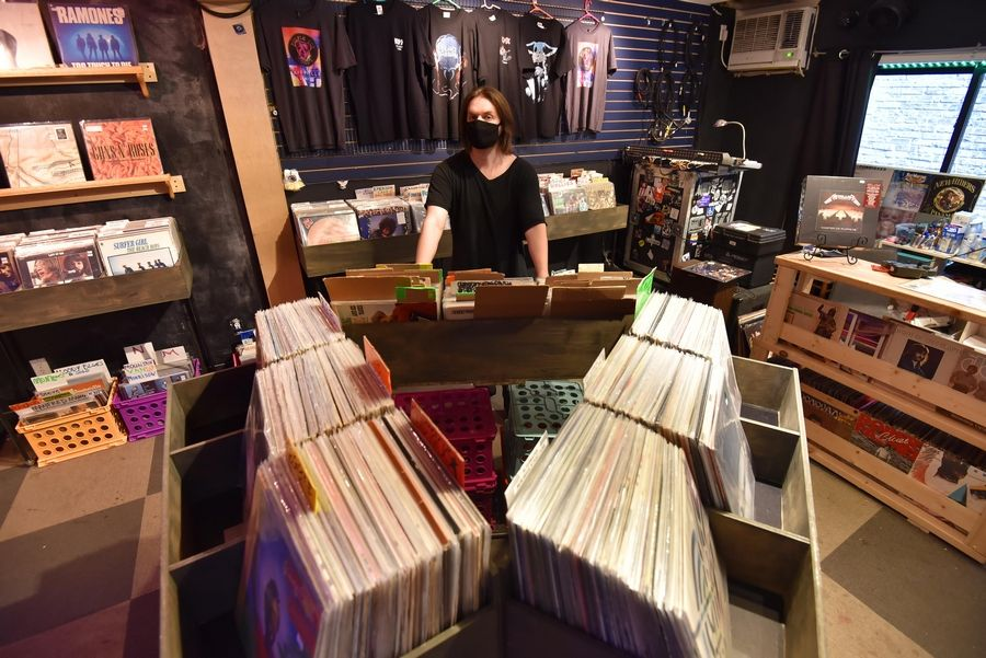 Colin Sicker manages Purple Dog Records on Wednesday in downtown Naperville on its second day in business at a new location. The shop closed March 15 because its building on Center Street in Naperville was sold, then it moved into an alley-front space at 231 S. Washington St., suite 105.