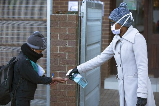 A pupil's hands are sanitised on returning to school in Johannesburg, Monday July 6, 2020, as more learners were permitted to return to class. Schools were shut down in March prior to a total country lockdown in a bid to prevent the spread of coronavirus and are now slowly being re-opened.
