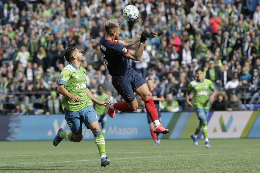 Chicago Fire defender Francisco Calvo, center, heads the ball in front of Seattle Sounders midfielder Cristian Roldan, left, during the first half of an MLS soccer match Sunday, March 1, 2020, in Seattle.