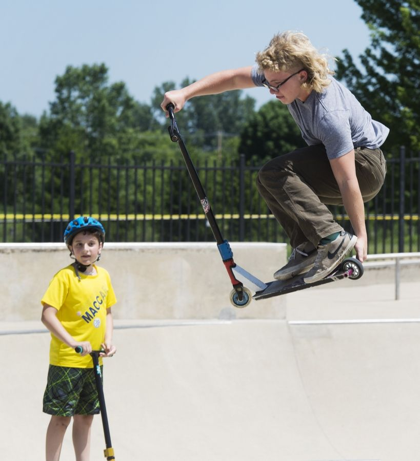 Nick Auberger of Elkhorn, Wis., goes airborne on his scooter as Daniel Mudrick, 12, of Northbrook watches at the Techny Prairie Park and Fields skate park in Northbrook recently. Auberger said his family had come to Northbrook to purchase a vehicle fender at a nearby body shop, and dropped him off at the park for a short while.