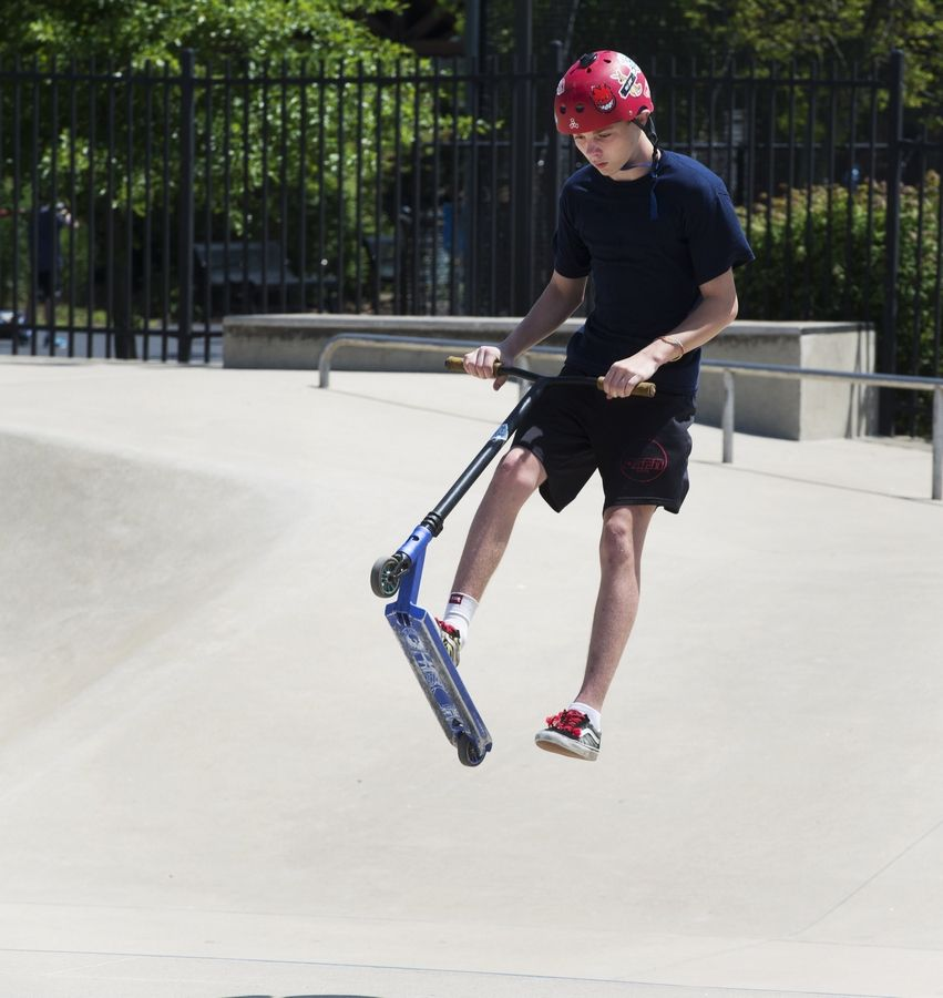 James Schnettler, 13, of Northbrook makes a jump on his scooter at Northbrook's Techny Prairie Park and Fields skate park.