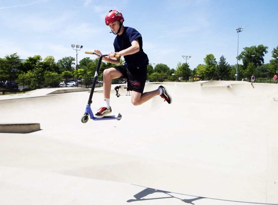 James Schnettler, 13, of Northbrook jumps on his scooter at the Techny Prairie Park and Fields skate park in Northbrook recently.