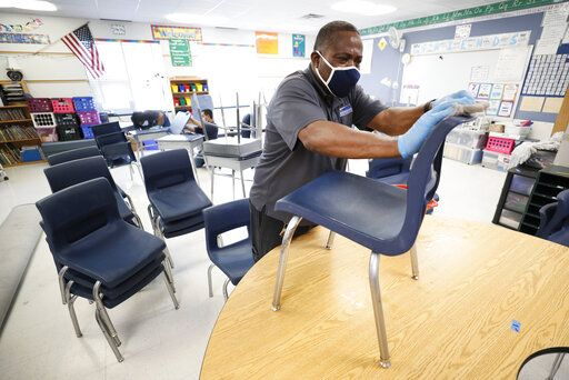 Des Moines Public Schools custodian Tracy Harris cleans chairs in a classroom at Brubaker Elementary School, Wednesday, July 8, 2020, in Des Moines, Iowa. Getting children back to school safely could mean keeping high-risk spots like bars and gyms closed. That's the latest thinking from some public health experts.