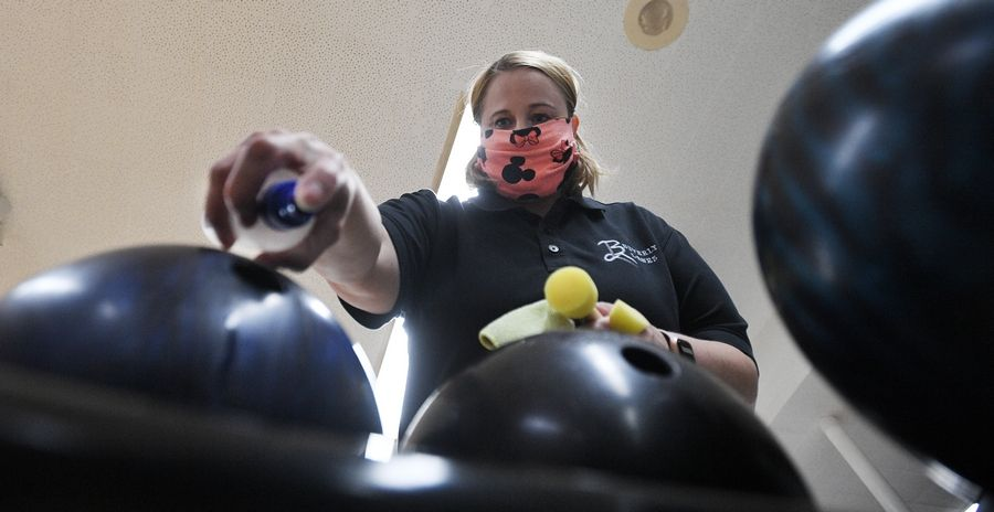 Manager Roxanne Brod, 42, of Rolling Meadows wipes down the bowling balls and swaps the finger holes after they are used by patrons at Beverly Lanes in Arlington Heights.