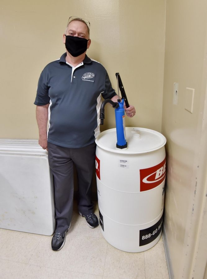 Stardust Bowl general manager Jim Saffold stands with the 55 gallon drum of hand sanitizer he has in Addison. The bowling alley has 84 lanes but only 50 people are allowed inside at a time.