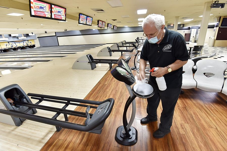 Stardust Bowl employee Pando Gllafce disinfects equipment in the large bowling alley in Addison. It has 84 lanes but only 50 people are allowed inside at a time.
