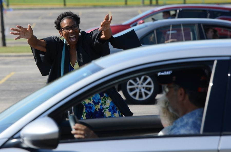 "Warren Township High School librarian Beryl Washington waves to graduating seniors Sunday during a drive-though graduation ceremony at the Almond Campus. ""I love it. It just warms my heart,"" Washington said."