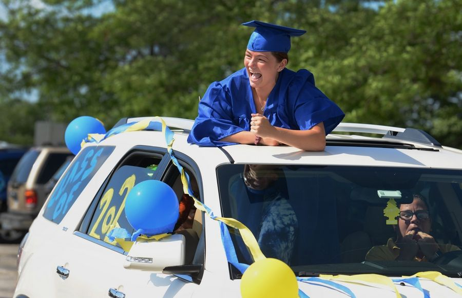 Warren Township High School senior Katlynn Breneisen of Gurnee celebrates Sunday during the parade of cars through the Almond Campus parking lot.