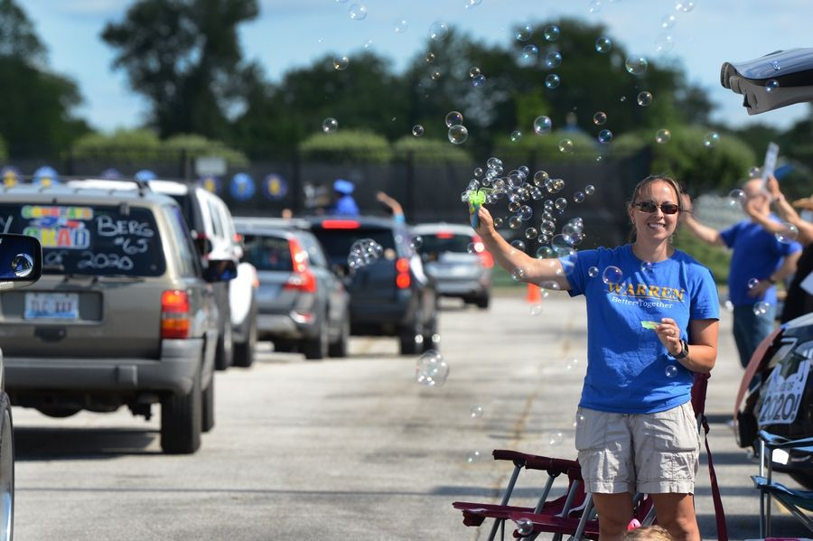 Warren Township High School college and career counselor Cari McGhan celebrates with the seniors during the parade of cars through the Almond Campus parking lot during the school's graduation on Sunday.