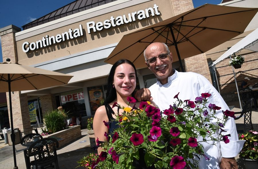 Continental Restaurant owner Pete Panayiotou and his daughter, Arai Panayiotou, show off the new flowers purchased by customers at the Buffalo Grove eatery. Last week someone stole flower pots from the restaurant's outdoor dining area.