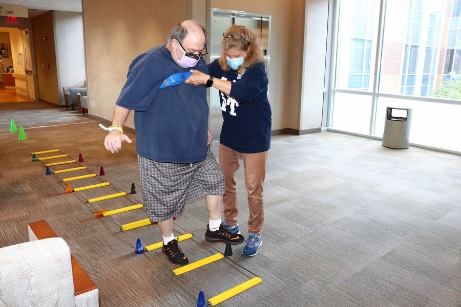 Julie Dahl, a physical therapist at Marianjoy Rehabilitation Hospital in Wheaton, helps COVID-19 survivor Chuck Drungelo with an exercise.