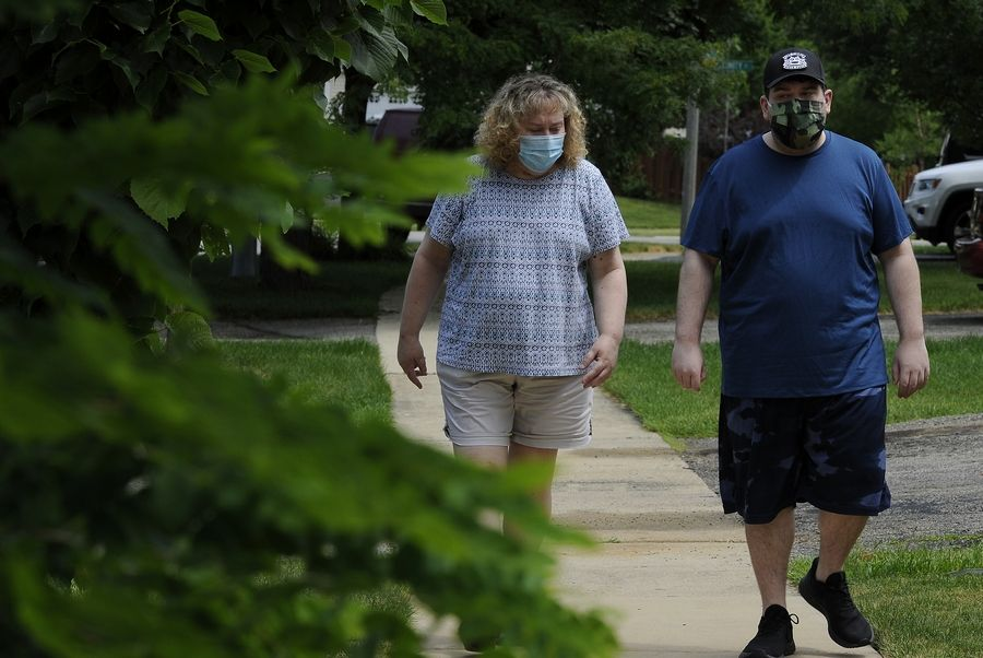 COVID-19 survivors Diane Drungelo, 53, and her son Jordan, 25, take a walk near their Carol Stream home as they recover from some lingering weakness.