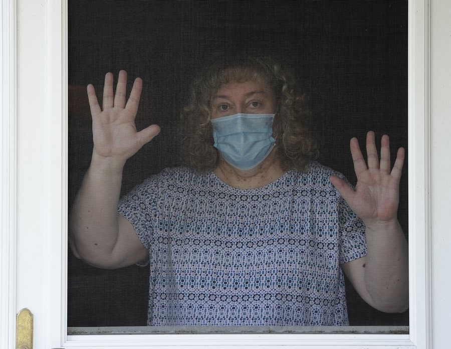 "COVID-19 survivor Diane Drungelo, 53, looks out from behind her screen door of her Carol Stream home. ""I'm concerned that people are not taking it as seriously as they should,"" she says of the virus."