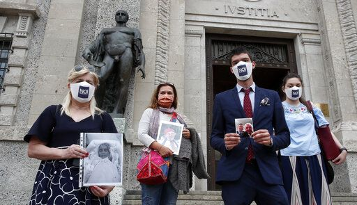 FILE - In this June 10, 2020 file photo, members of Noi Denunceremo (We will denounce) Facebook group, from left, Laura Capella, Nicoletta Bosica, Stefano Fusco and Arianna Dalba holds pictures of their relatives, victims of COVID-19, as they stand in front of Bergamo's court, Italy, Wednesday, June 10, 2020. Noi Denunceremo and affiliated non-profit committee are filing 100 new cases Monday, July 13, 2020, with Bergamo prosecutors, on top of 50 complaints lodged last month.