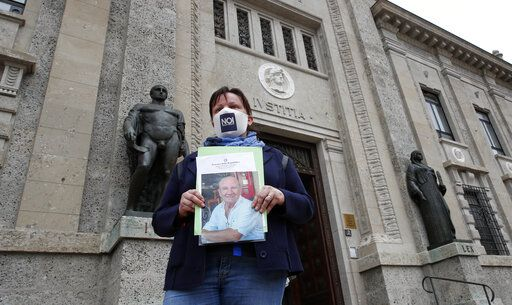 FILE - In this June 10, 2020 file photo, member of Noi Denunceremo (We will denounce) Facebook group, Laura Silvestri holds up a photograph of her father Giuseppe, a COVID-19 victim, in front of Bergamo's court, Italy, Wednesday, June 10, 2020. Noi Denunceremo and affiliated non-profit committee are filing 100 new cases Monday, July 13, 2020, with Bergamo prosecutors, on top of 50 complaints lodged last month.