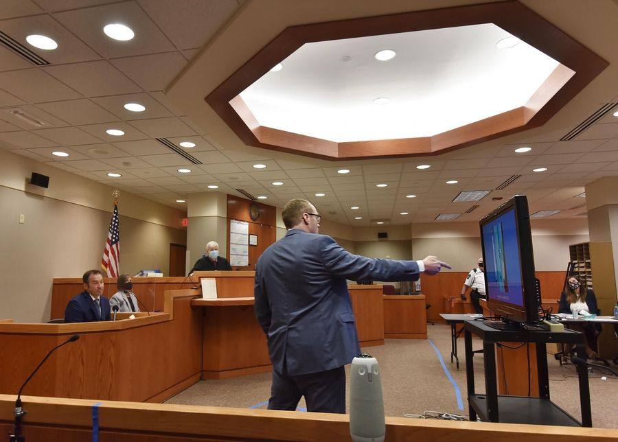 McHenry County State's Attorney Patrick Kenneally points to photographs on a flat screen as Crystal Lake police officer Brian Burr testifies Thursday during the JoAnn Cunningham's sentencing hearing in Woodstock. The photos were of the Cunningham home on Dole Avenue in Crystal Lake.