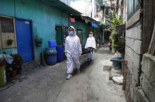 Funeral home workers in protective suits carry a body during the start of a lockdown due to a rise in COVID cases in the city of Navotas, Manila, Philippines on Thursday, July 16, 2020. Coronavirus infections continue to rise in the country after reopening the economy that is on the brink of a recession while still struggling to combat the pandemic. The cause of death is unconfirmed.