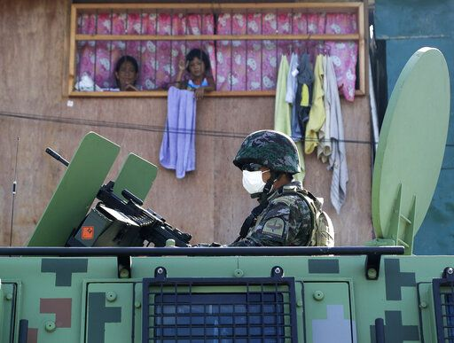 Residents watch as a police officer rides atop an Armored Personnel Carrier by their home during the start of a lockdown due to a rise in COVID cases in the city of Navotas, Manila, Philippines, Thursday, July 16, 2020. Coronavirus infections continue to rise in the country after reopening the economy that is on the brink of a recession while still struggling to combat the pandemic.
