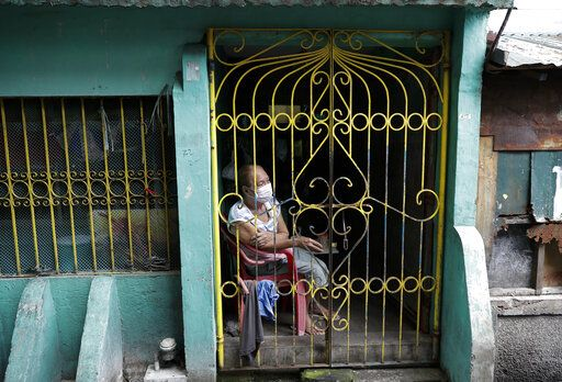 A resident sits inside her home during the start of a lockdown due to a rise in COVID cases in the city of Navotas, Manila, Philippines, Thursday, July 16, 2020. Coronavirus infections continue to rise in the country after reopening the economy that is on the brink of a recession while still struggling to combat the pandemic.