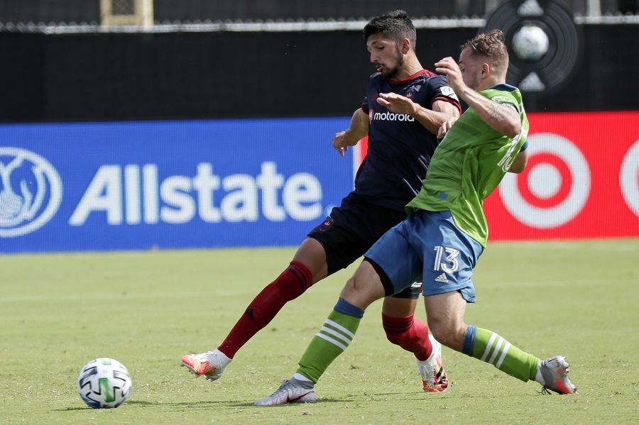 Chicago Fire defender Mauricio Pineda, left, and Seattle Sounders forward Jordan Morris (13) fight for position on the ball during the second half of an MLS soccer match, Tuesday in Kissimmee, Fla.