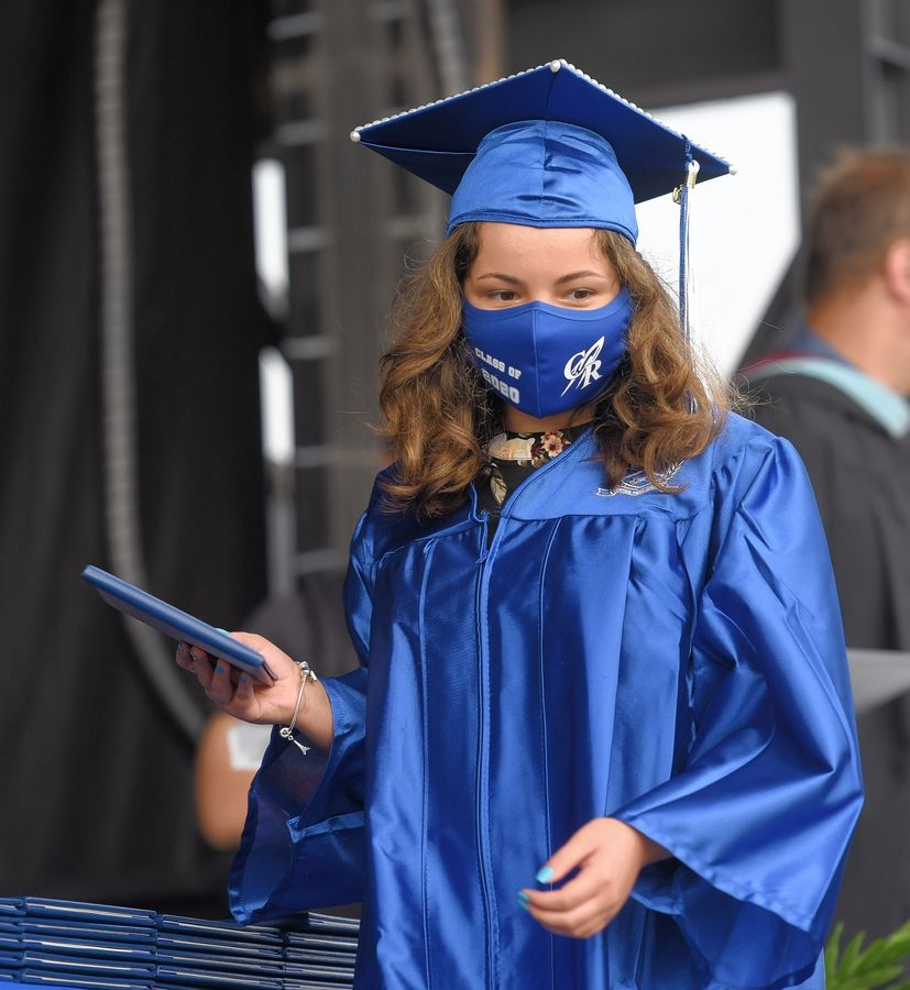 Julianna Rodriguez receives her diploma during the 2020 Burlington Central High School graduation ceremony Saturday in the parking lot of the Sears Centre in Hoffman Estates.