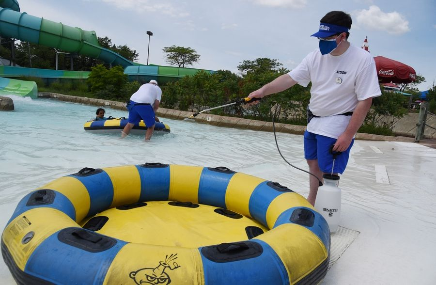 Team member Greyson Cox disinfects a tube Monday at Hurricane Harbor Chicago in Gurnee. The water park opened for the first time this season on Monday, with new safety protocols including mask and social distancing requirements.