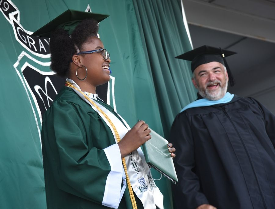 Grayslake Central High School graduate Edah Tumuti smiles for a photo to the delight of Principal Dan Landry during Wednesday's graduation ceremony in the school's parking lot.