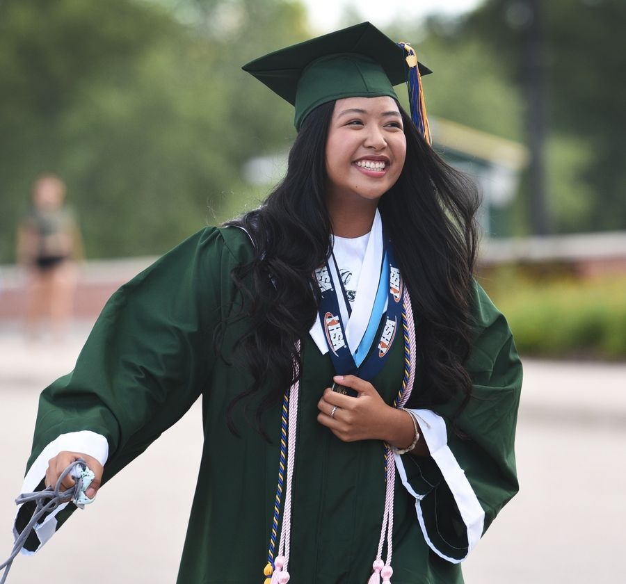 Grayslake Central High School's Jennica Sajor shows her joy after walking across the stage at a socially distanced graduation ceremony Wednesday evening in the school's parking lot.