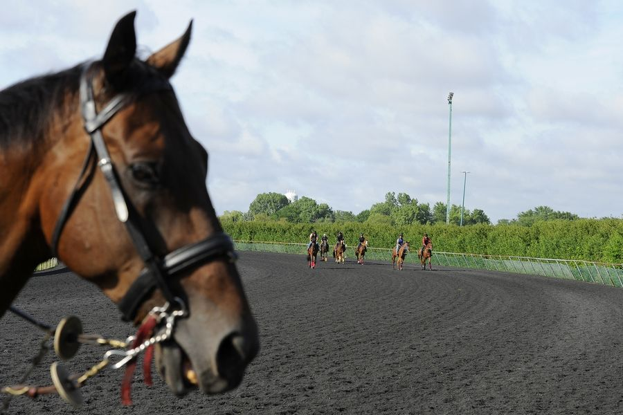 Exercise riders work out their race horses on the day before Arlington Racecourse will open without fans.