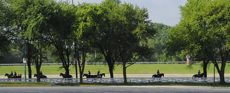 Exercise riders head to the track to work the race horses on the day before Arlington racecourse will open without fans.