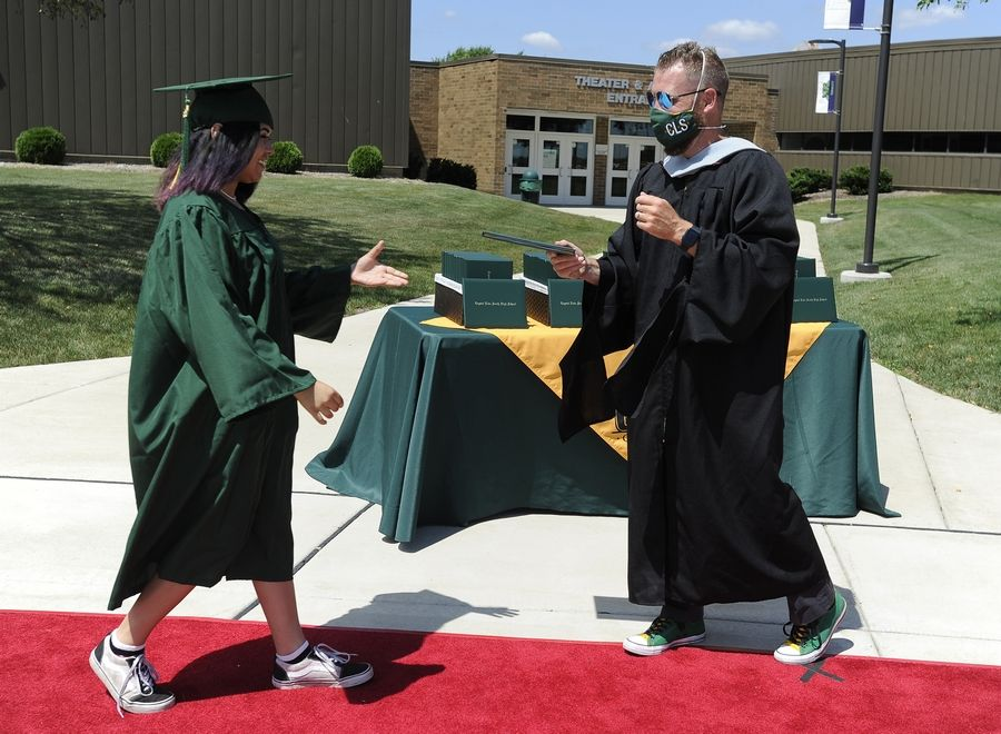 Crystal Lake South High School graduate Maya Alvarez, 18, of Crystal Lake receives her diploma from Principal Josh Nobilio Friday at the school.